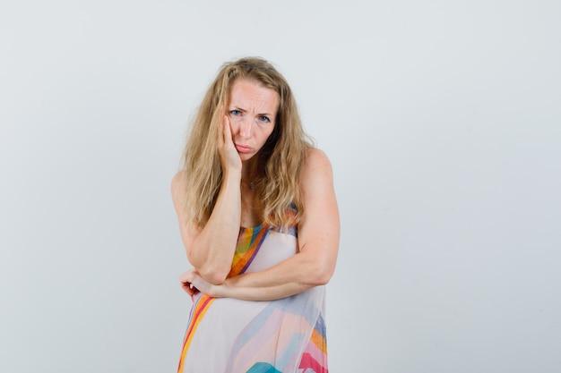 Młoda dama opierając uniesioną dłoń na policzku w letniej sukience i patrząc smutno.