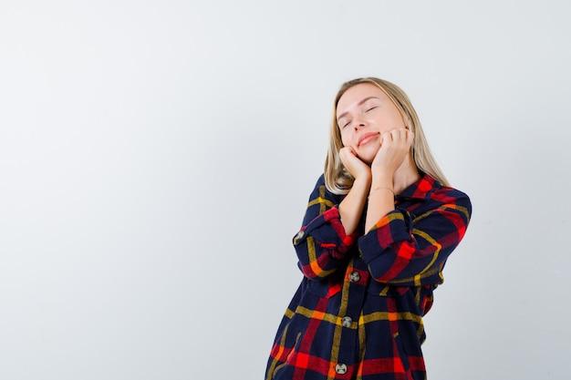 Młoda dama otula twarz rękami w kraciastej koszuli i wygląda na śpiącą. przedni widok.