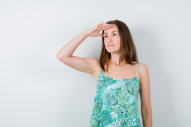 Młoda dama patrząc daleko z ręką nad głową i patrząc skupiony, widok z przodu.