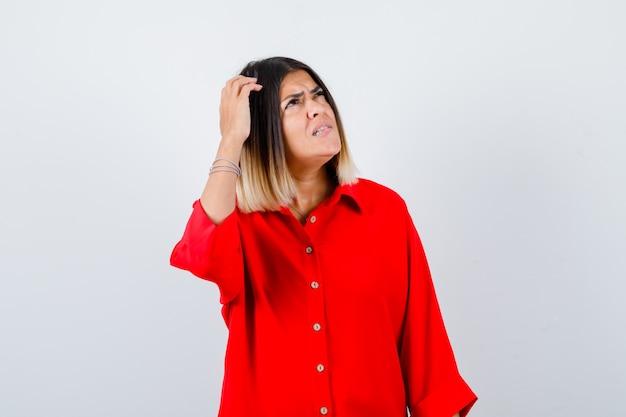 Młoda dama patrząc na bok, drapiąc się po głowie w czerwonej koszuli oversize i patrząc zamyślony, widok z przodu.