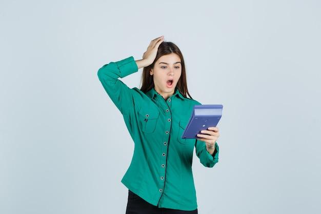 Młoda dama patrząc na kalkulator, trzymając rękę na głowie w zielonej koszuli i patrząc zszokowany, widok z przodu.