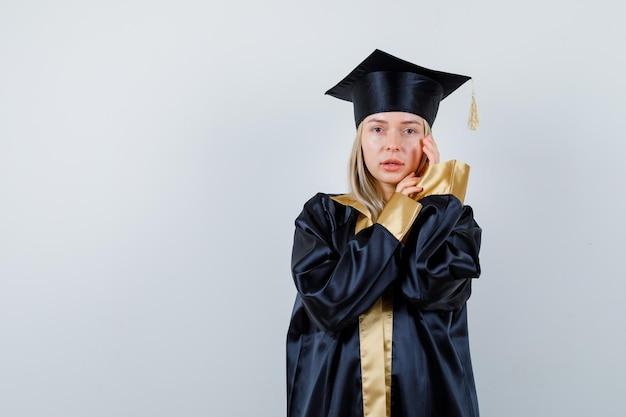 Młoda dama patrząc na kamery podczas pozowanie w akademickim stroju i patrząc zmartwiony.