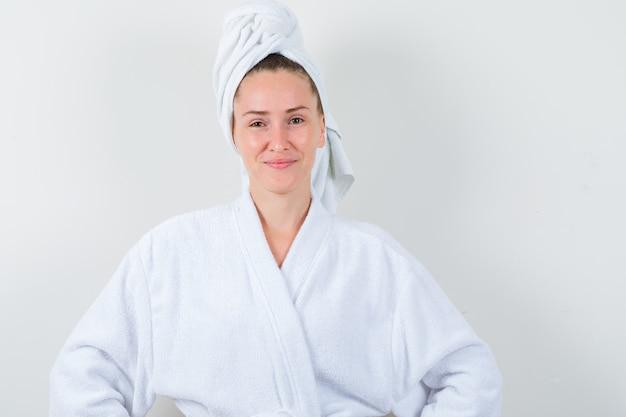 Młoda dama patrząc na kamery w biały szlafrok, ręcznik i wyglądający wesoło, widok z przodu.
