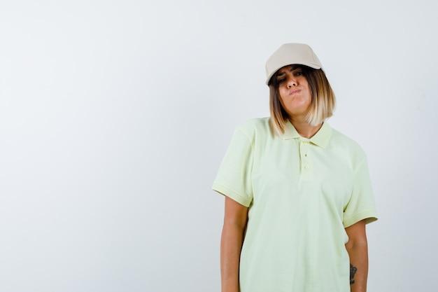 Młoda dama patrząc na kamery w koszulce, czapce i tęsknie patrząc, widok z przodu.