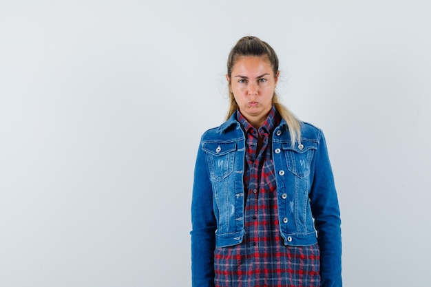 Młoda dama patrząc na kamery w koszuli, kurtce i uparty widok z przodu.
