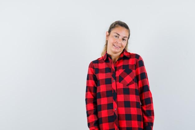 Młoda dama patrząc na kamery w kraciastej koszuli i wyglądająca na zawstydzoną