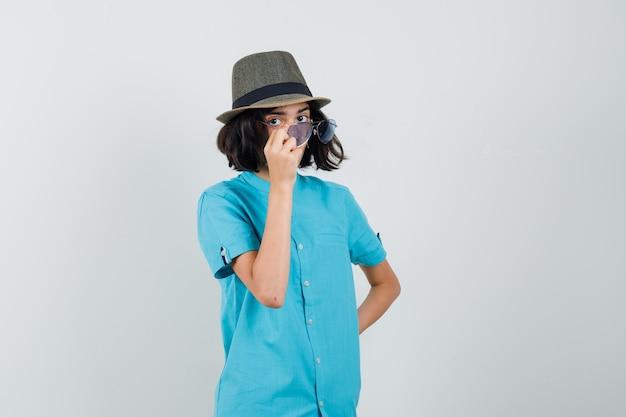 Młoda dama patrząc na okulary w niebieskiej koszuli, okulary przeciwsłoneczne