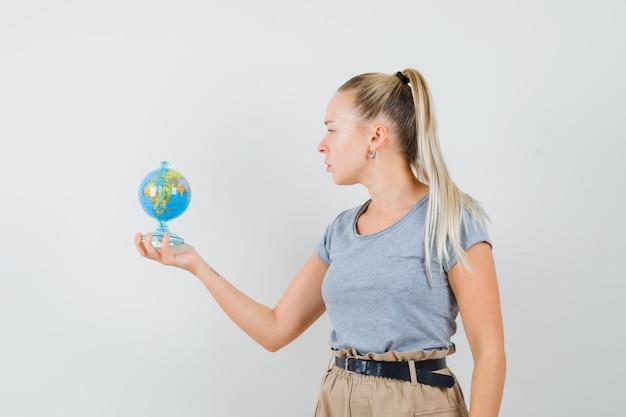 Młoda dama patrząc na szkolnej kuli ziemskiej w t-shirt i spodnie