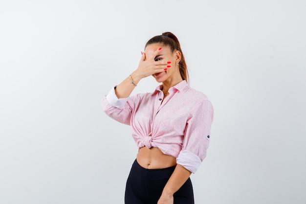 Młoda dama patrząc przez palce w koszuli, spodniach i wyglądająca zaciekawiona
