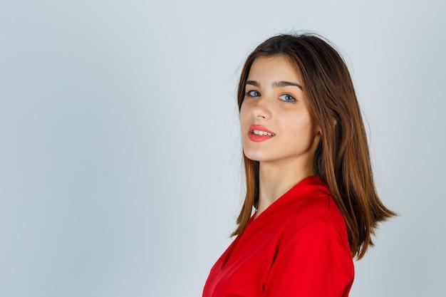 Młoda dama patrząc przez ramię w czerwonej bluzce i wyglądająca uroczo