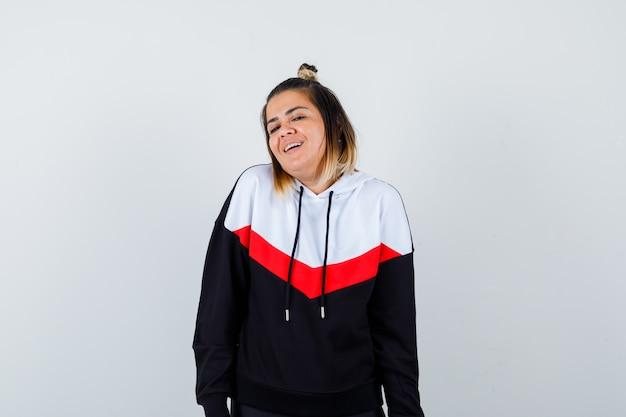 Młoda dama patrząca bezpośrednio w sweter z kapturem i wyglądająca na radosną.