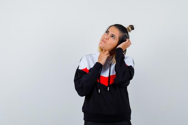 Młoda dama patrząca w górę, drapiąc się po głowie w swetrze z kapturem i wyglądająca na zamyśloną