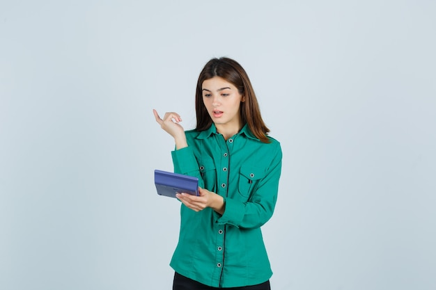 Młoda dama patrzy na kalkulator, pokazując gest eureki w zielonej koszuli i wyglądająca na zaskoczoną. przedni widok.