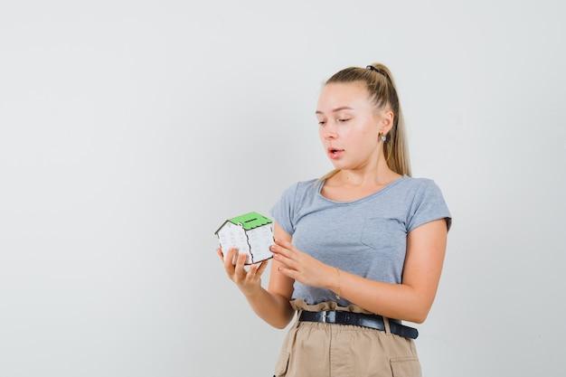 Młoda dama patrzy na model domu w t-shirt i spodnie i wygląda na zdumionego