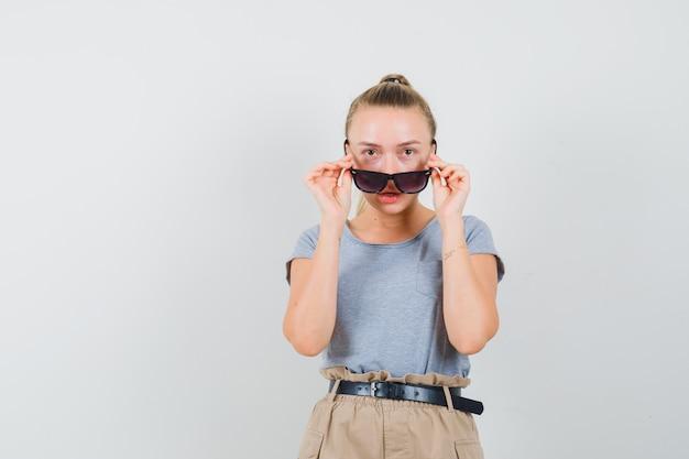 Młoda dama patrzy na okulary w t-shircie i spodniach i wygląda na wątpliwą