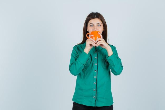 Młoda dama pije herbatę z pomarańczowego kubka w koszuli i wygląda pewnie. przedni widok.