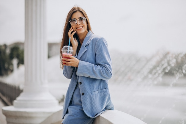 Młoda dama pije mrożoną herbatę w parku i rozmawia przez telefon