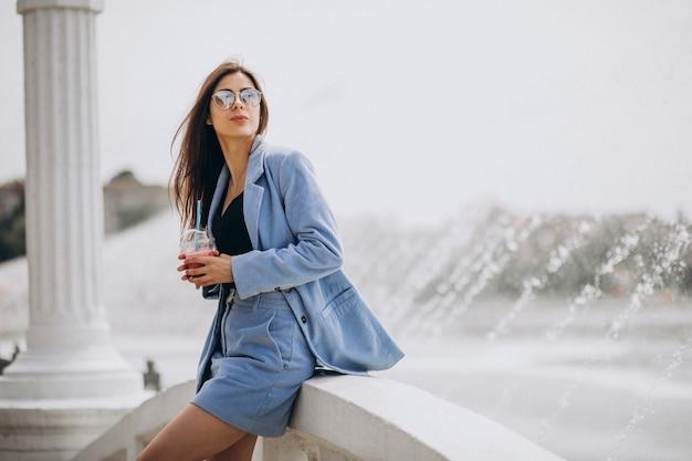 Młoda dama pije mrożoną herbatę w parku