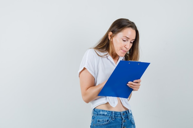 Młoda dama pisze coś w schowku w białej bluzce, widok z przodu.