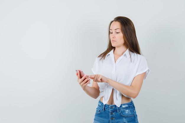 Młoda dama pisze wiadomość w białej bluzce i wygląda na skoncentrowaną. przedni widok. miejsce na tekst