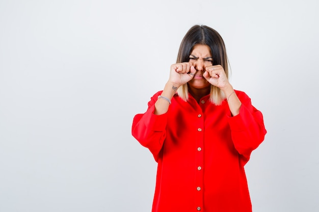 Młoda dama płacze, przecierając oczy rękami w czerwonej koszuli oversize i wygląda na smutną, widok z przodu.