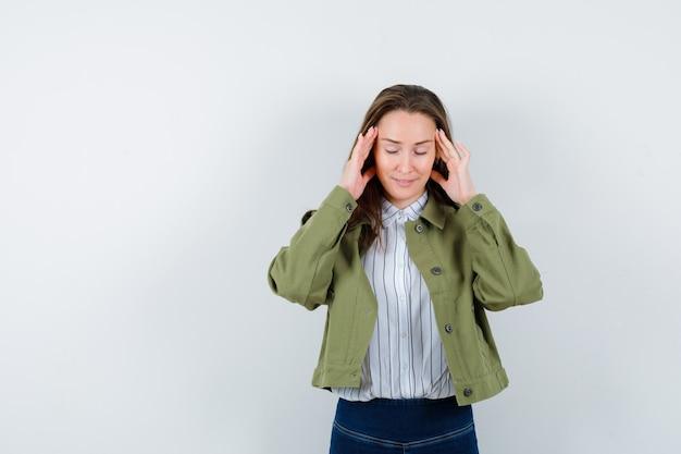 Młoda dama pociera skronie w bluzce, kurtce i wygląda marzycielsko. przedni widok.