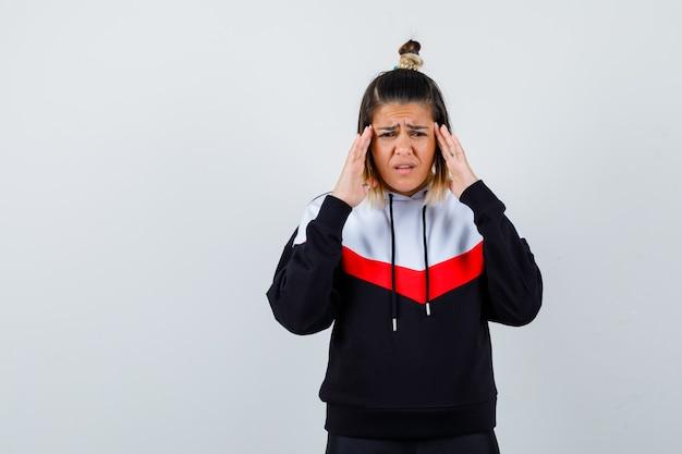 Młoda dama pociera skronie w sweter z kapturem i wygląda na smutną.