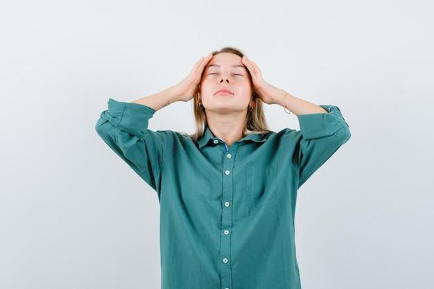 Młoda dama pociera skronie w zielonej koszuli i wygląda na zrelaksowaną