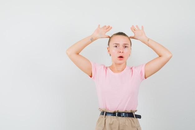 Młoda dama podnosi dłonie w geście kapitulacji w t-shircie i spodniach i wygląda na przestraszoną