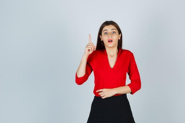 Młoda dama podnosi palec wskazujący w geście eureki w czerwonej bluzce