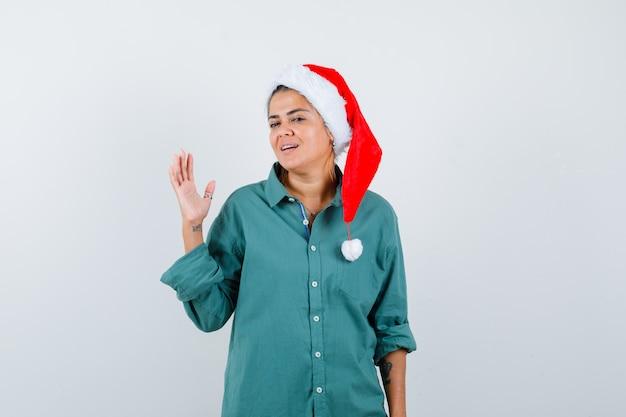 Młoda dama podnosząc rękę w świątecznym kapeluszu, koszuli i patrząc wesoło. przedni widok.