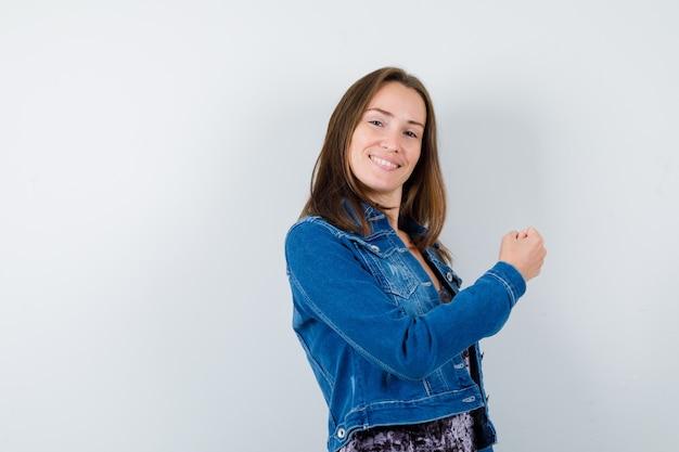 Młoda dama podnosząca pięść w bluzce, dżinsowej kurtce i patrząc na szczęśliwego, widok z przodu.