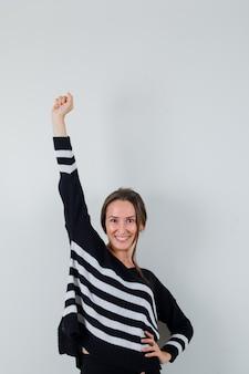 Młoda dama podnosząca ramię w koszuli i wyglądająca na szczęśliwą