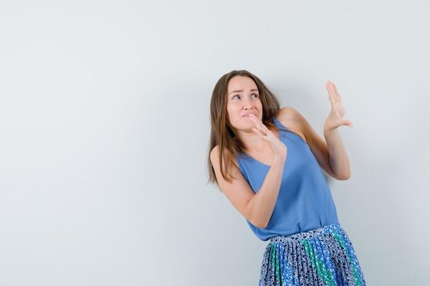 Młoda dama podnosząca ręce, by bronić się przed czymś w niebieskiej bluzce, spódnicy i wyglądająca na zaniepokojoną, widok z przodu.