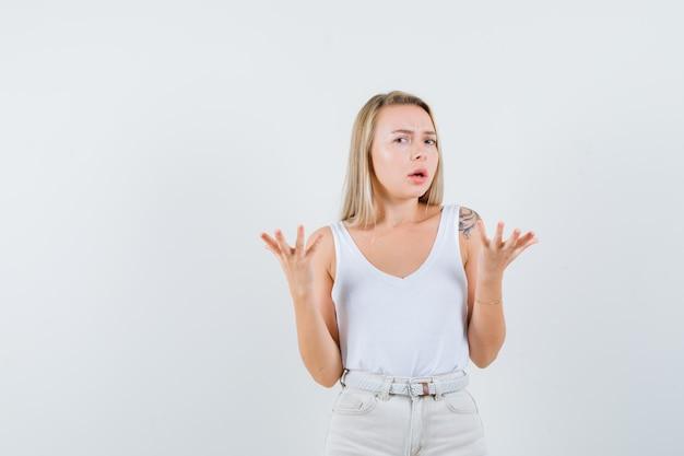 Młoda dama podnosząca ręce z otwartą dłonią w białej bluzce i wyglądająca na zdziwioną