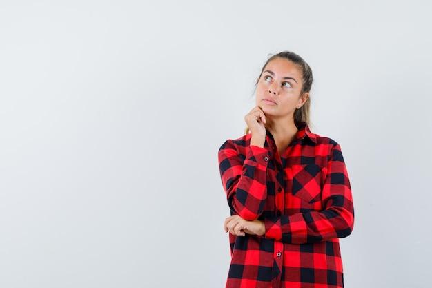 Młoda dama podpiera brodę na pięści w kraciastej koszuli i wygląda zamyślona