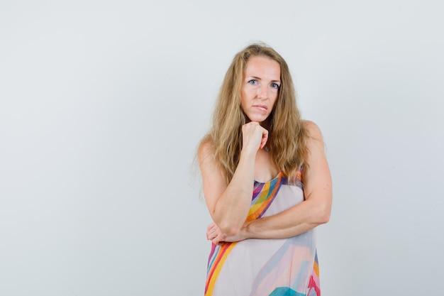 Młoda dama podpiera podbródek na podniesionej pięści w letniej sukience i wygląda zamyślona.