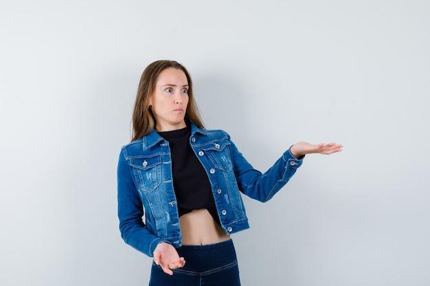 Młoda dama pokazując coś w bluzce, kurtce, dżinsach i patrząc zdziwiony, widok z przodu.