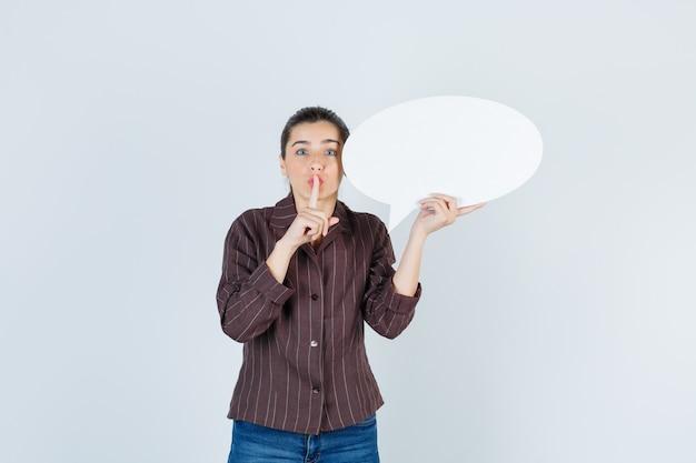 Młoda dama pokazując gest ciszy, trzymając papierowy plakat w koszuli, dżinsach i patrząc poważnie, widok z przodu.