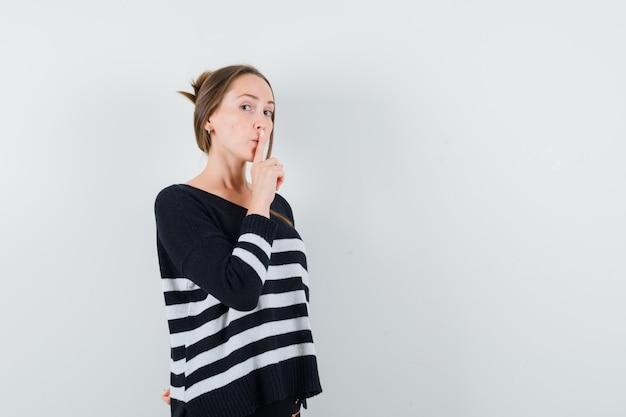 Młoda dama pokazując gest ciszy w swobodnej koszuli i patrząc ostrożnie