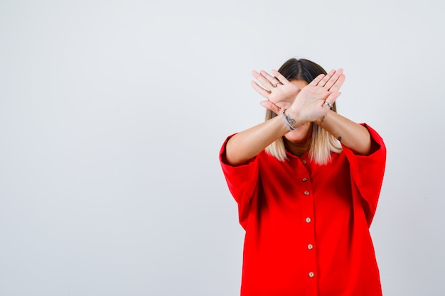 Młoda dama pokazując gest odmowy w czerwonej koszuli oversize i patrząc pewnie, widok z przodu.