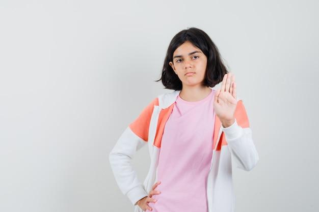 Młoda dama pokazując gest pożegnania w kurtce, różowej koszuli i patrząc poważnie.