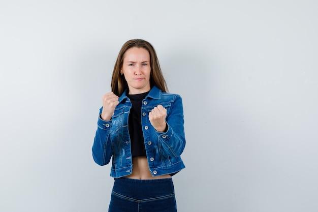 Młoda dama pokazując gest zwycięzcy w bluzkę, kurtkę, dżinsy i patrząc pewnie, widok z przodu.