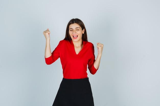 Młoda dama pokazując gest zwycięzcy w czerwonej bluzce, czarnej spódnicy i patrząc na szczęście