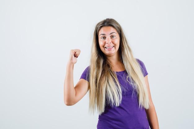 Młoda dama pokazując gest zwycięzcy w fioletowej koszulce i patrząc szczęśliwy, widok z przodu.