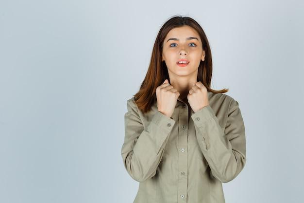 Młoda dama pokazując gest zwycięzcy w koszuli i patrząc na szczęście, widok z przodu.