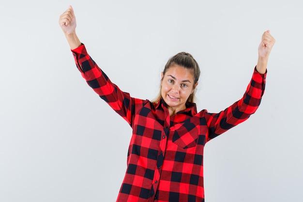 Młoda dama pokazując gest zwycięzcy w kraciastej koszuli i wyglądający na błogi