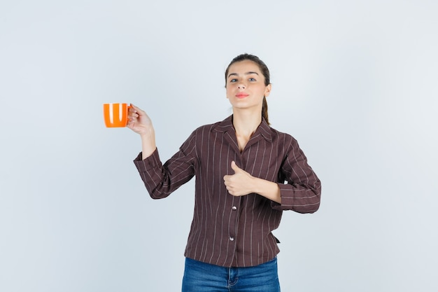 Młoda dama pokazując kciuk do góry, podnosząc kubek w koszuli, dżinsach i patrząc pewnie, widok z przodu.