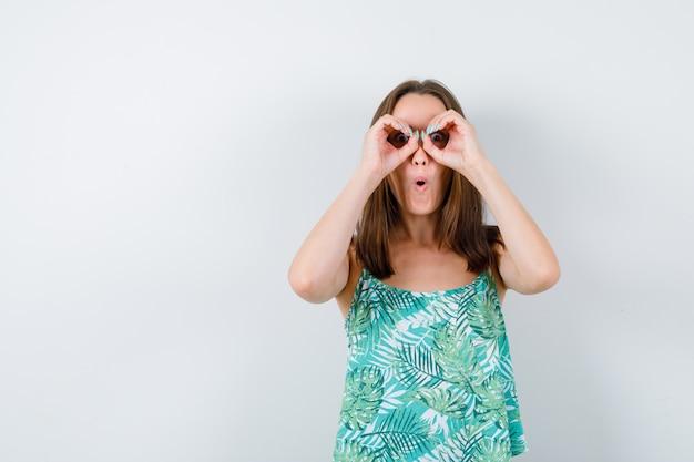 Młoda dama pokazując okulary gest i patrząc zdziwiony, widok z przodu.