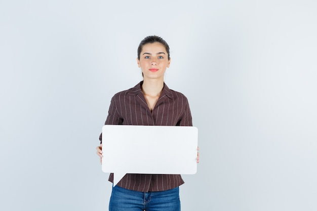 Młoda dama pokazując papierowy plakat w koszuli, dżinsach i patrząc poważnie, widok z przodu.